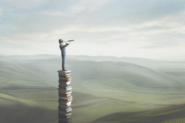 Uomo su pila di libri che scruta l'orizzonte tra verdi colline per allenare la fantasia